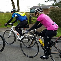 Two cyclists ride along a road