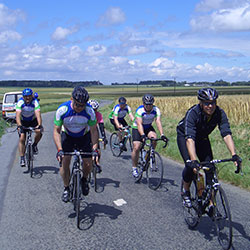a group of cyclists ride along a road